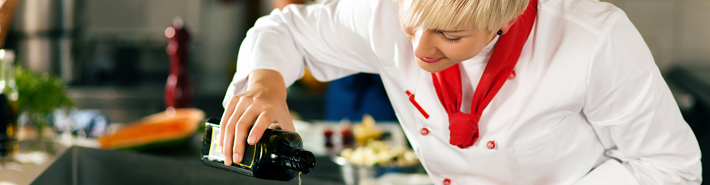 Chef in focus pouring oil in front of blurred background resembling a kitchen